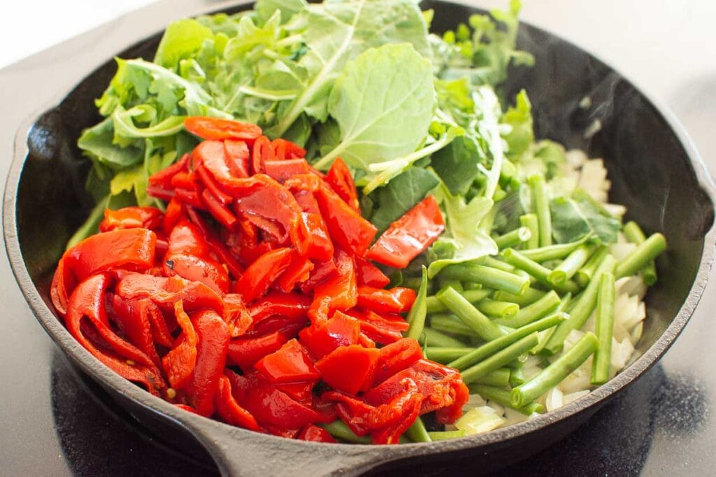 sauteed onion, roasted red peppers, green beans, greens in a skillet