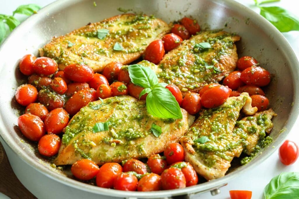 Horizontal image of Pesto Chicken in a pan with cherry tomatoes and basil