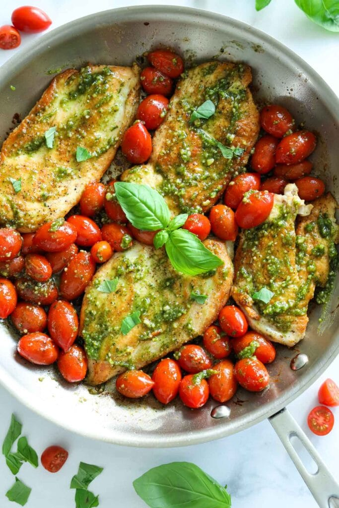 Pesto Chicken with cherry tomatoes and basil in a pan