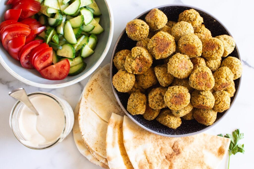 falafel in a bowl pitas on plate with tahini sauce and chopped cucumber tomatoes in a bowl