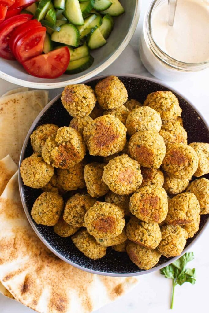 chickpea quinoa falafel piled in a bowl sauce and pita sandwich items