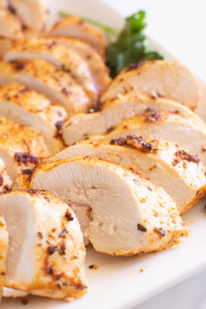 close up for air fryer chicken breast sliced on a plate with garnish