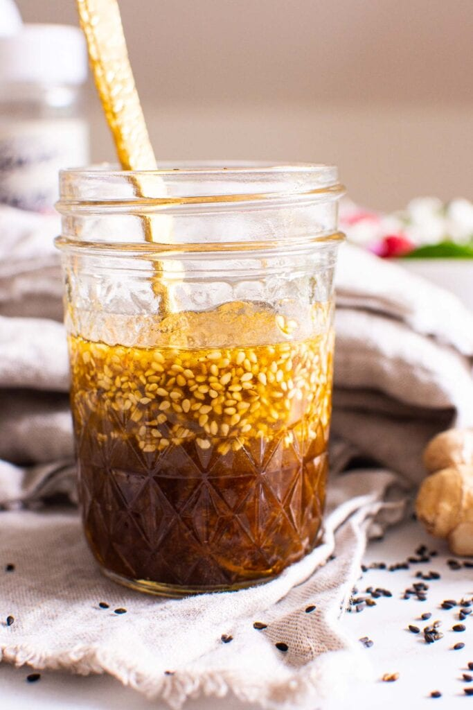 asian salad dressing in mason jar with sesame seeds and linen
