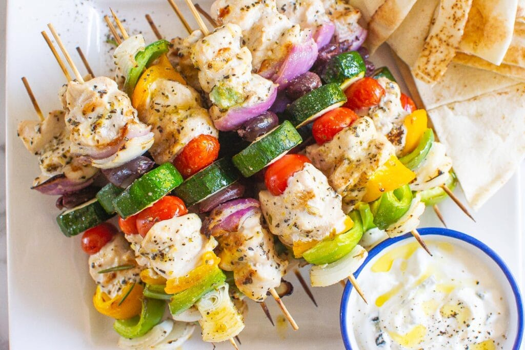 greek chicken kabobs on plate with sauce and pita