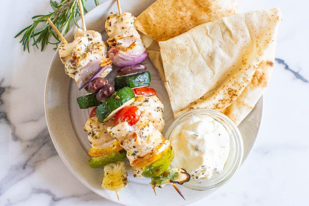 greek kabobs on plate with garnish sauce and pita