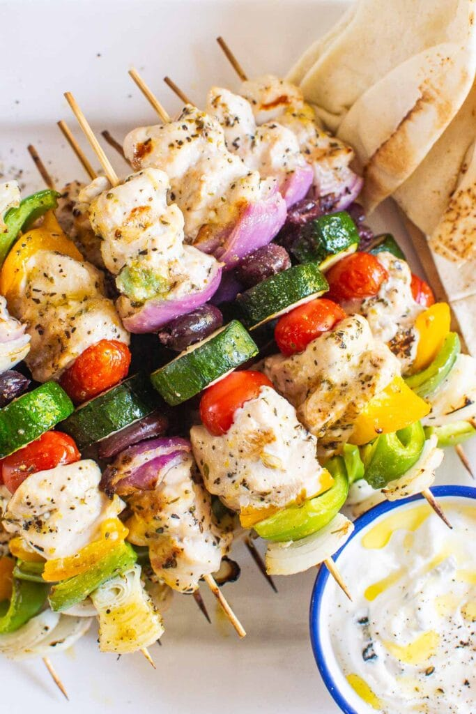 kabobs on skewers with sauce and pita on the side