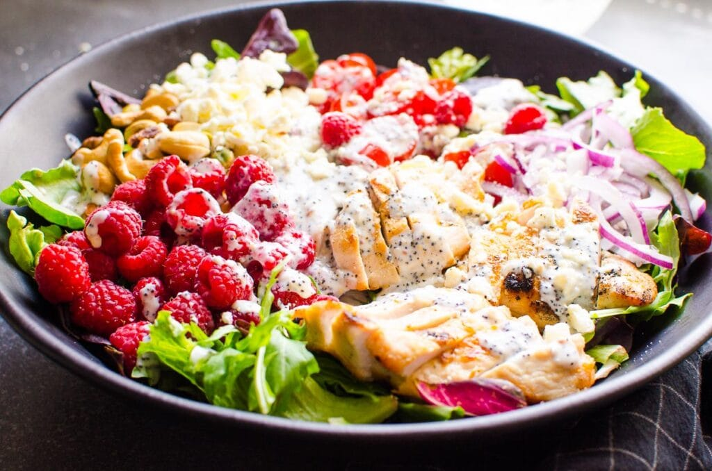 grilled chicken in a salad with dressing and raspberries