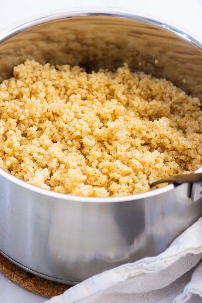 fluffy quinoa in pot with spoon
