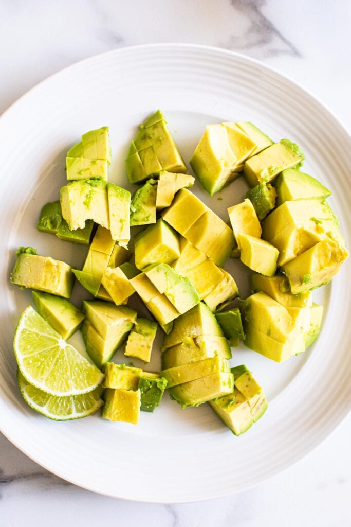 diced avocado with lime on plate