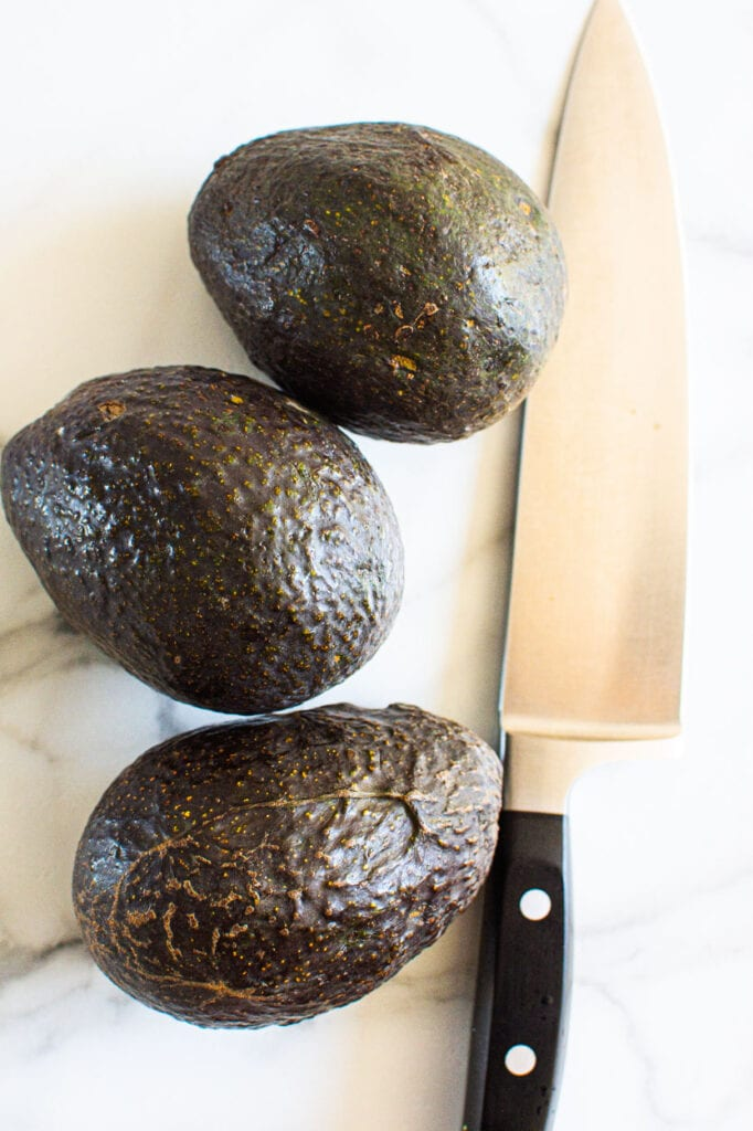3 avocados with knife