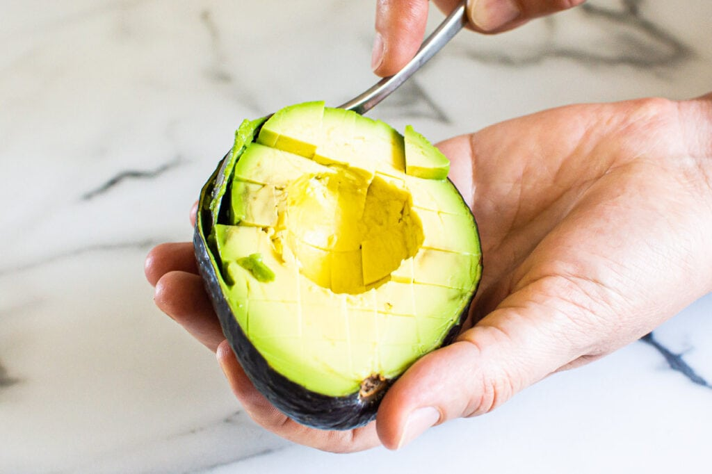 scooping out a cut avocado