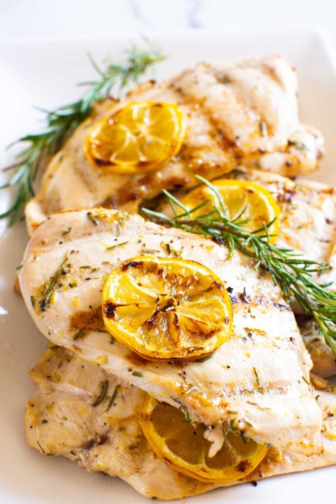 grilled lemon rosemary chicken breast in serving dish garnished with lemon and rosemary sprigs