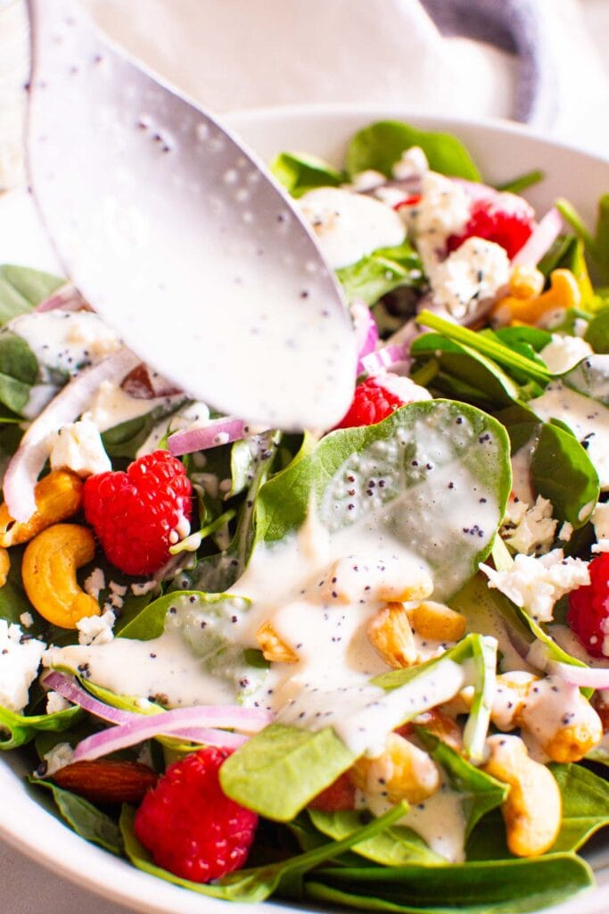 salad with poppy seed dressing dripping off of spoon into salad