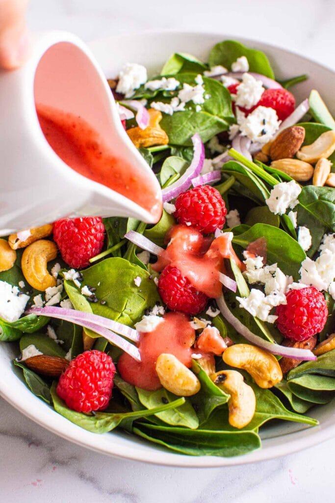 raspberry vinaigrette recipe being poured onto a salad