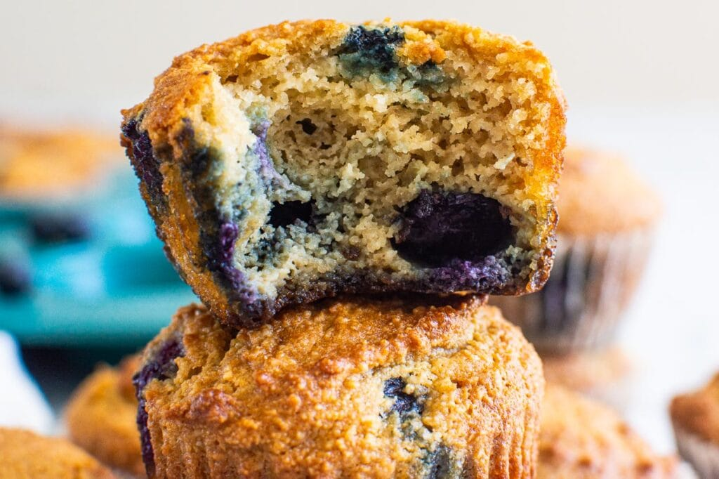 short stack of gluten free blueberry muffins with blue pan in background