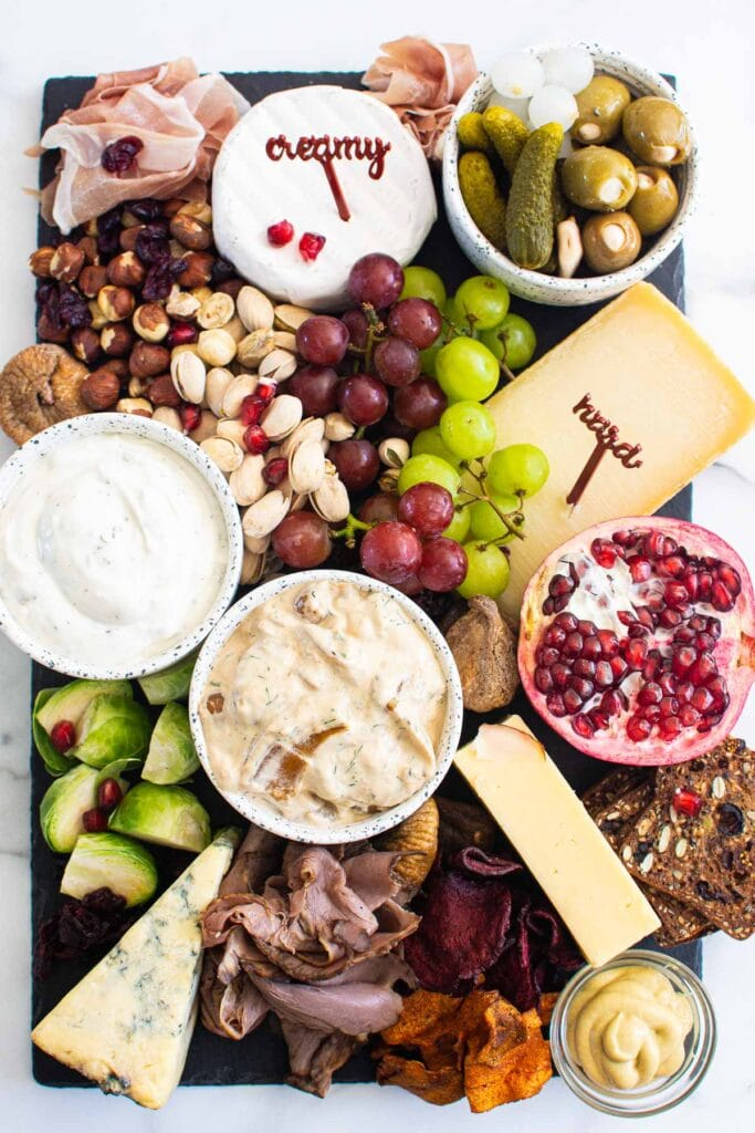 christmas charcuterie board with meats cheese fruit pickled veggies and nuts