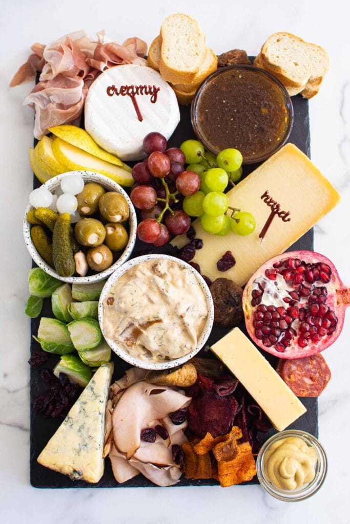 Thanksgiving charcuterie board with meats cheeses breads dips