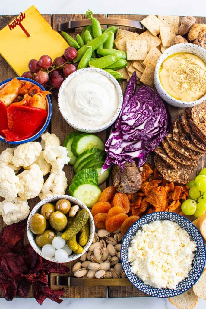 vegan charcuterie board with rainbow of vegetables dairy free cheese and breads