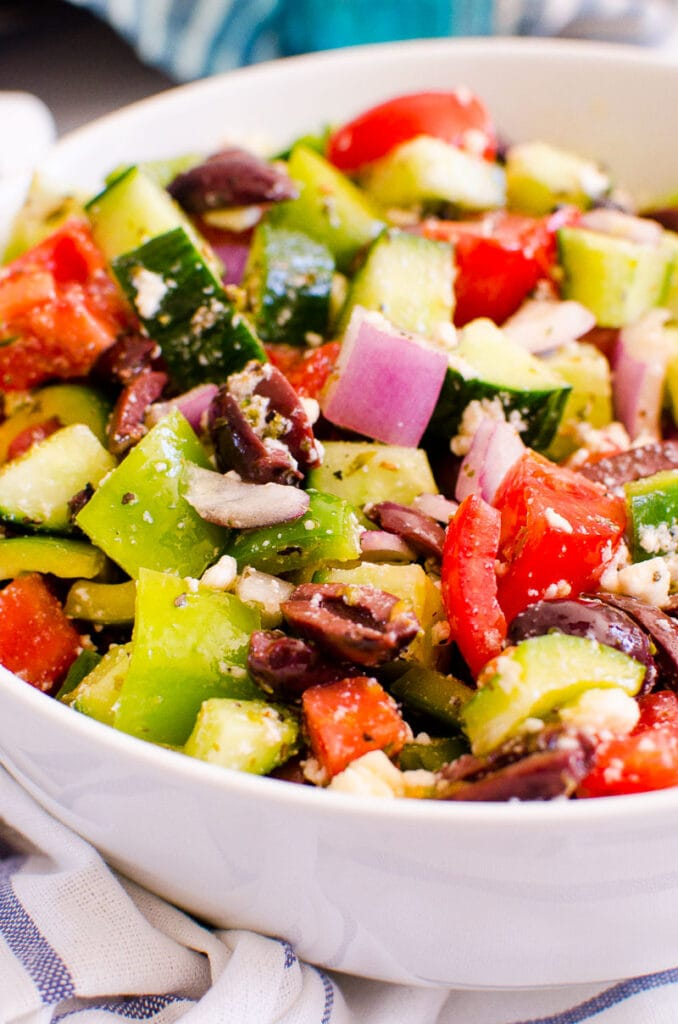 side shot of greek salad in a white bowl with linen