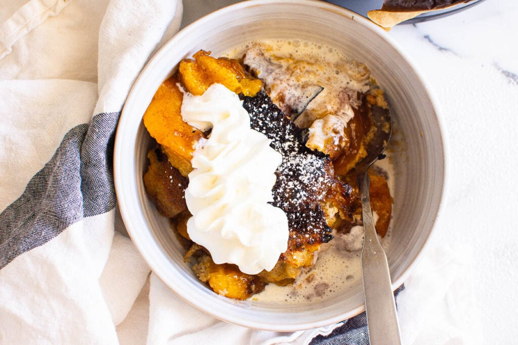 fruit cobbler made in instant pot with whipped cream and spoon
