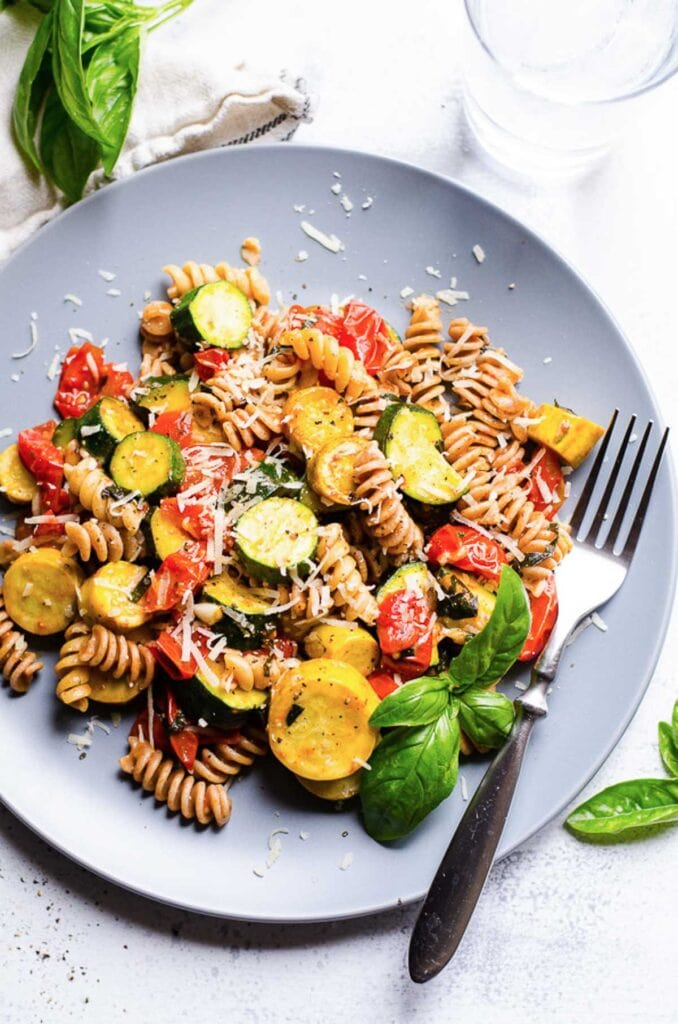 zucchini tomato pasta recipe with fresh basil on a plate with a fork