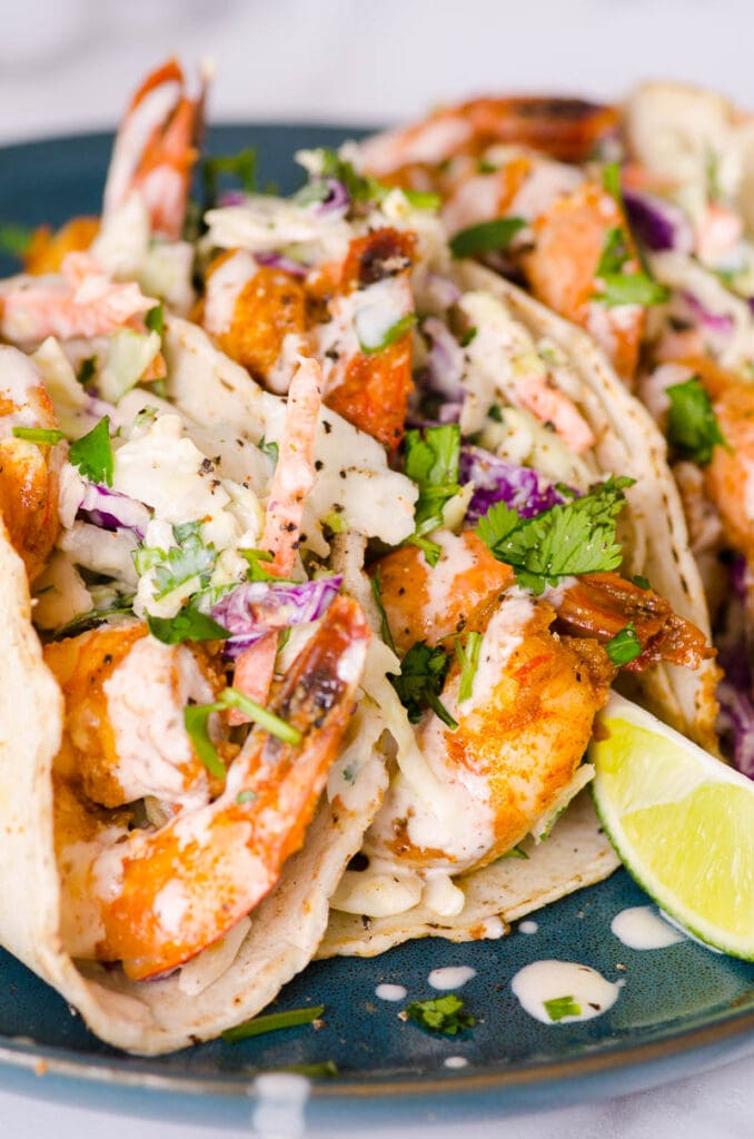 shrimp tacos on plate with lime wedge