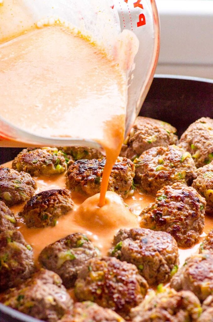 thai turkey meatballs with red curry sauce being poured on it