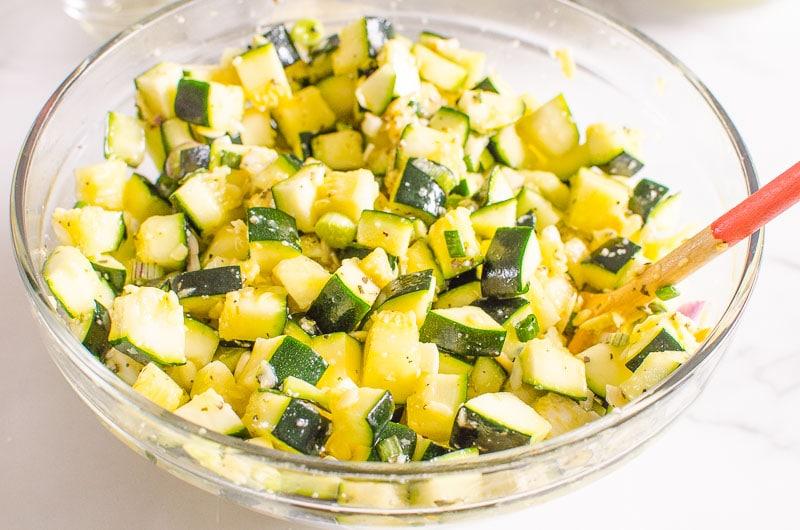 zucchini in a bowl getting mixed for zucchini casserole