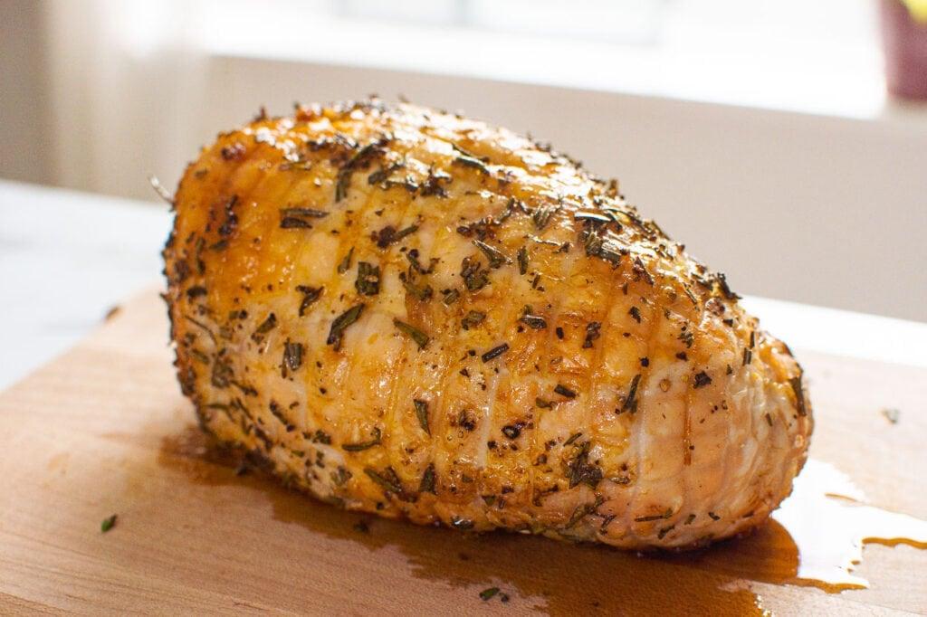 finished boneless skinless turkey breast roast on cutting board