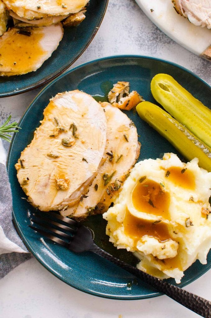 roast turkey breast recipe plated with mashed potatoes and gravy and pickles