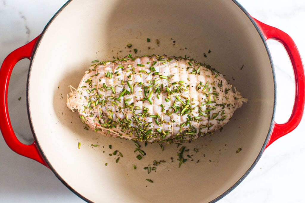 showing turkey breast in large dutch oven with herbs