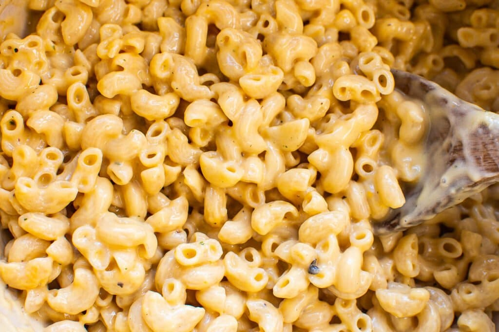 macaroni and cheese sprinkled with seasoning with a spoon dipped into it for serving