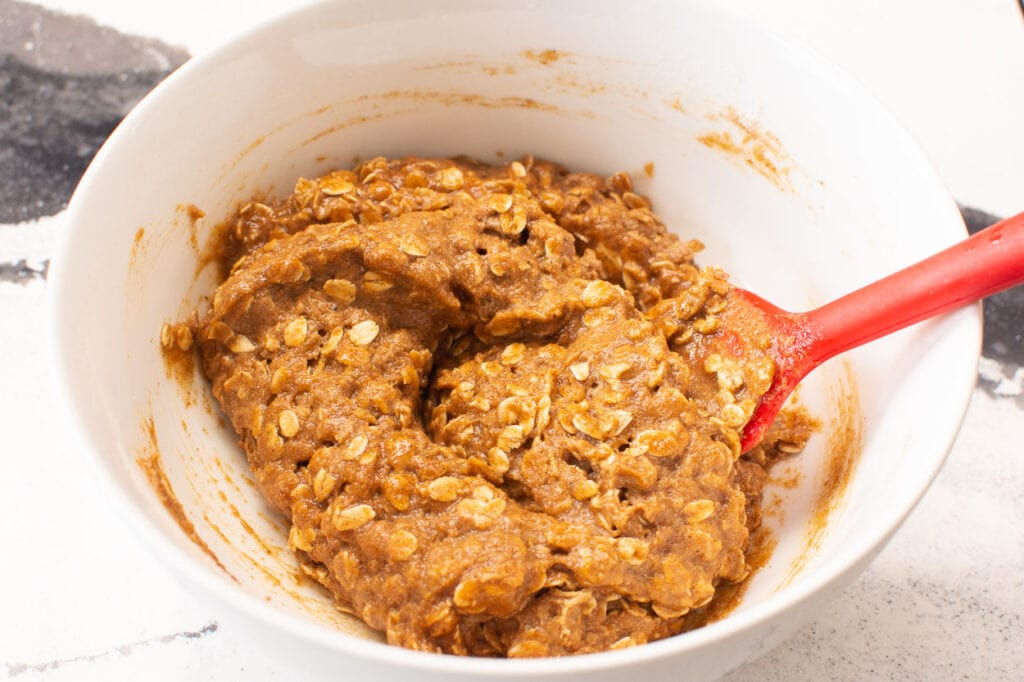 gently mixing pumpkin oatmeal cookie batter