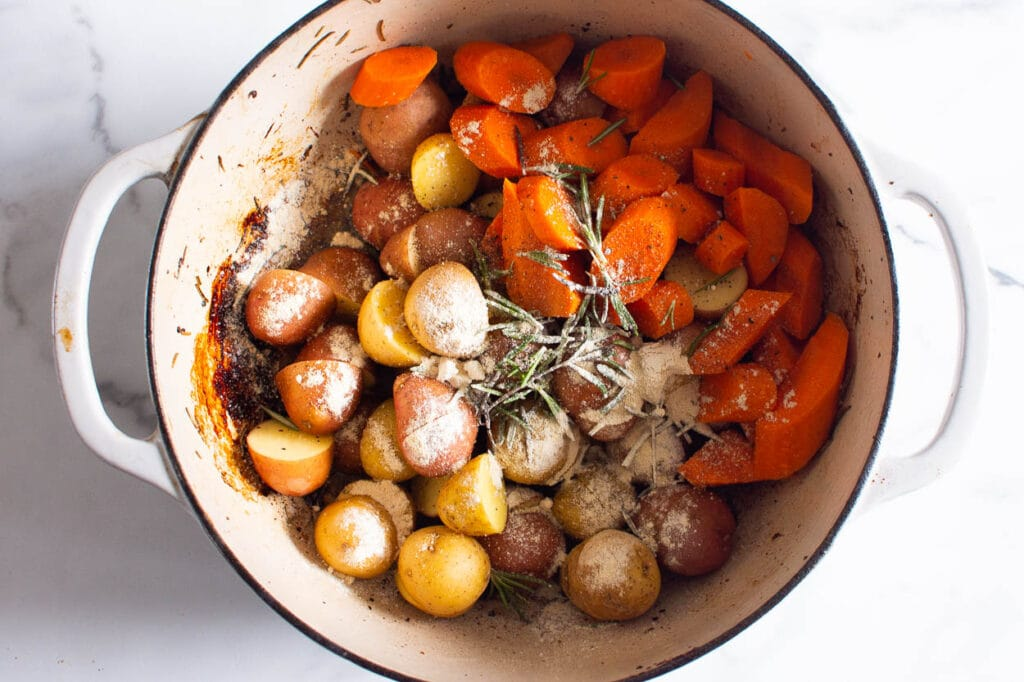 seasoned potatoes and carrots in dutch oven