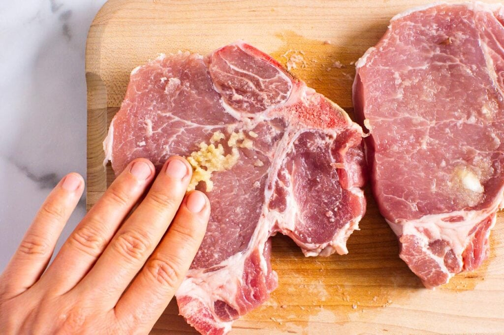 rubbing pork chop with grated garlic