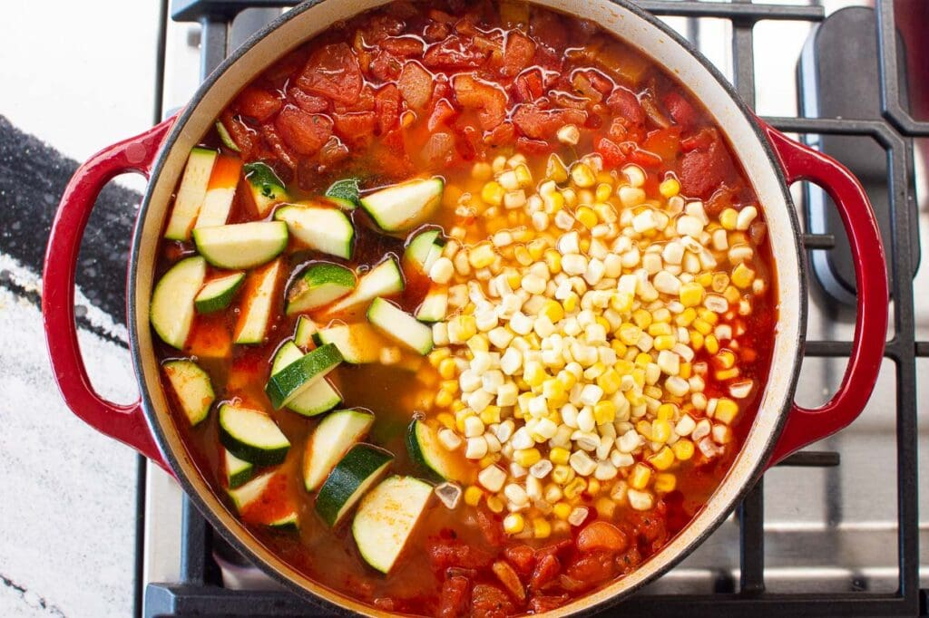 zucchini and corn in vegetable soup on the stove