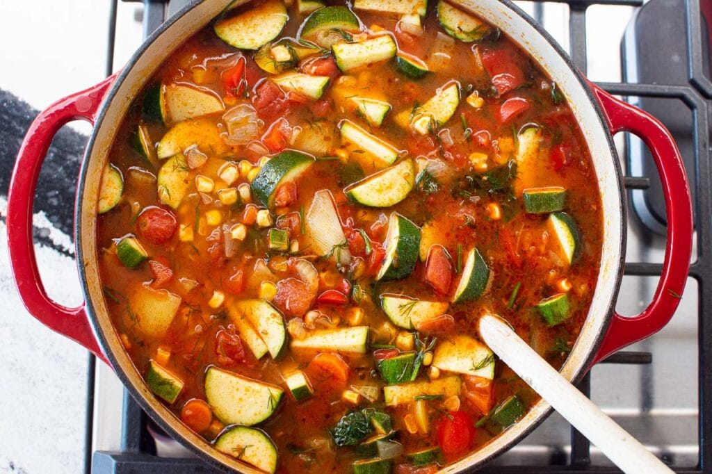 stirring soup with vegetables, fresh dill and garlic on stove