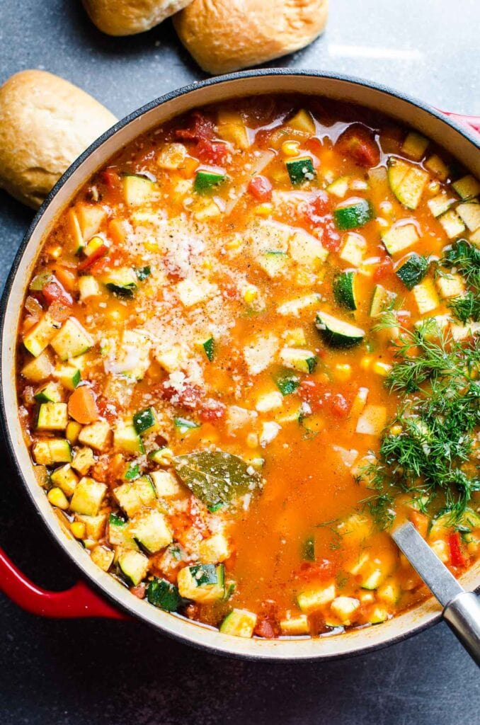 veggie soup in a large pot with crusty rolls behind it