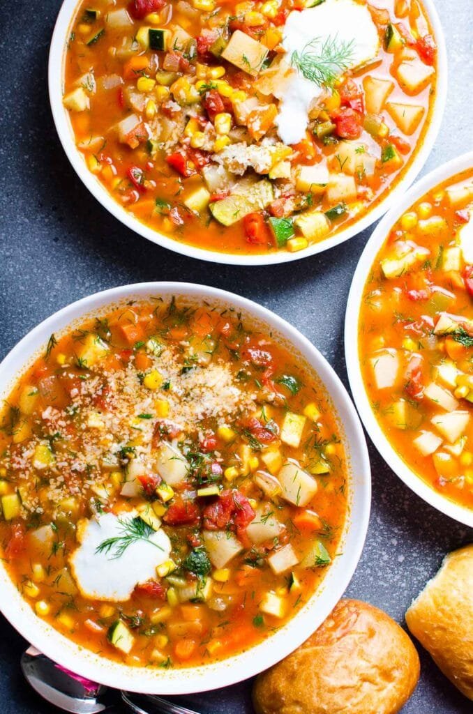 three bowls of vegetable soup with greek yogurt dill and parmesan garnish served with rolls